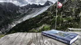 A rugged view of the Swiss Alps with a Swiss flag and a book detailing the Haute Route from Chamonix to Zermatt on a wooden, rustic table