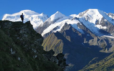 A walker on the Haute Route trek looks at the snowy mountains while standing on a stony mountain peak