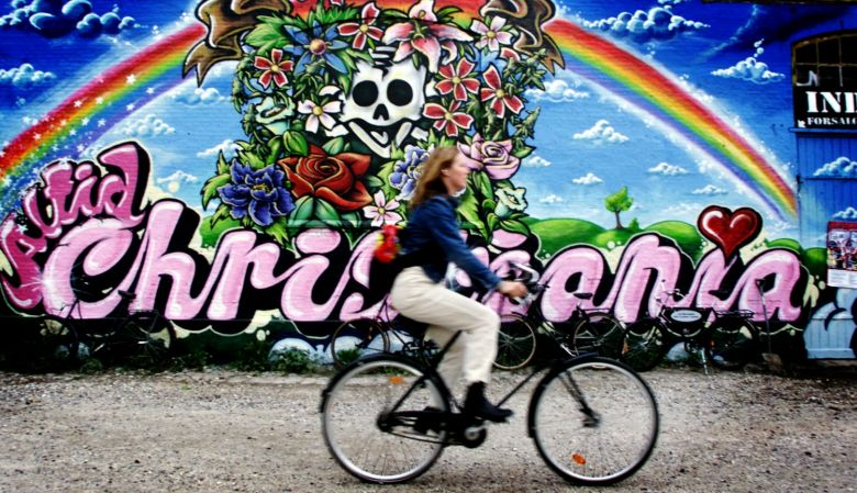 A person riding a bike past colourful graffiti in Copenhagen's free town Christiania