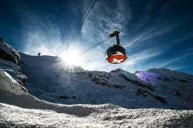Titlis Rotair, chair lift, ski lift, sun breaking through the mountains, swiss flag