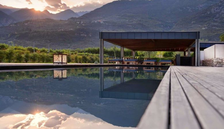 Vivere Suites outdoor elongated Swimming pool | sunset over the Arco Mountains of Trentino in Italy close to Lake Garda.
