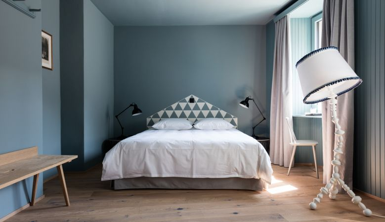 Boutique bedrooms of the design Hotel de Londres Brig Switzerland, a small meeting venue in the heart of the Valais Alps, interiors in blue and accents of wallas culture, creative bedrooms, elegance