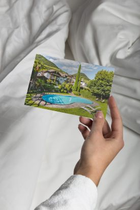 A person looking at a postcard of the pool at | Magdalener Hof | Bolzano, Italy
