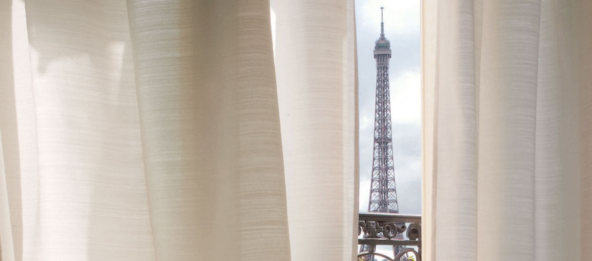 View of the Effel Tower Paris from behind the curtains of the luxury La Reserve Apartments, Trocadéro, France