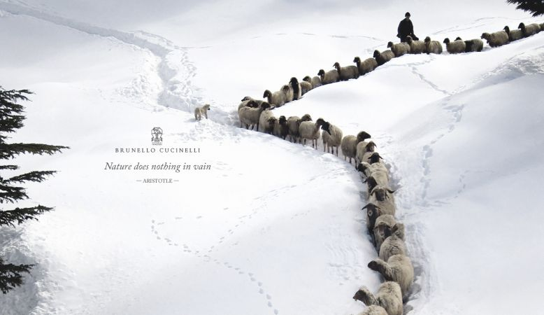 Sheep being herded down a snowy mountain for fashion house Moessmer