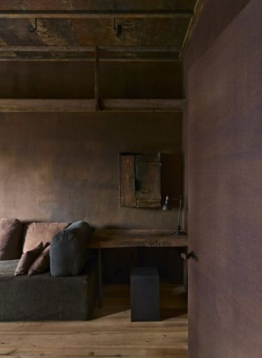A photo of the interior of The Greenwich Hotel penthouse by iconic interior designer Axel Vervoordt who works with wabi-sabi, the sofa and the corner of the room