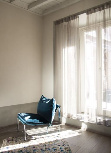 The interior design of hotel CasaCau, Rome, a blue chair by a sunlit window