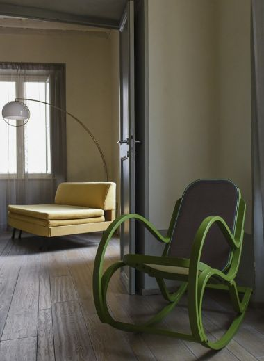 The interior design from Rome's hotel CasaCau, a green rocking chair foreground, a yellow lazing chair background