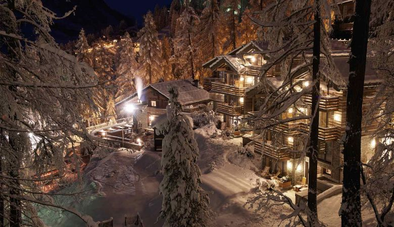 The designer CERVO Boutique Mountain Resort in Zermatt overlooking the Matterhorn, as featured in Zurmatt, Switzerland, extior snowy mountain lodge, nighfall image, magical lighting