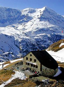 Mountain hut for the Haute Route in the Alps, snowy peaks in the background