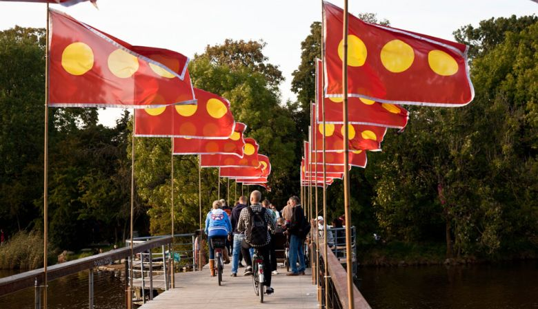 People riding bikes over a bridge over the lake in Copenhagen's free town Christiania