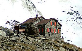 Mountain hut for the Haute Route in the Alps, snowy mountain in the background