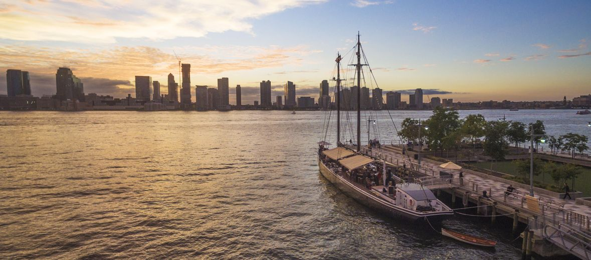 Sun set image form TriBeCa showing floating dining Grand Banks restuarant at pier 25 NYC