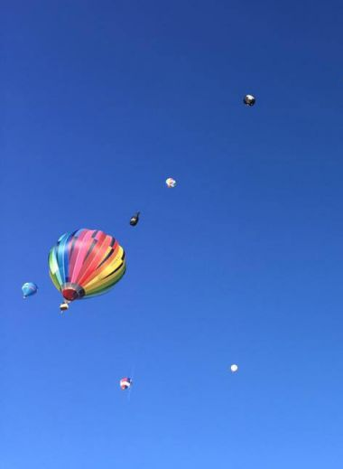 A colourful photo of Switzerland's famous hot air balloon festival, blue sky and balloons in it