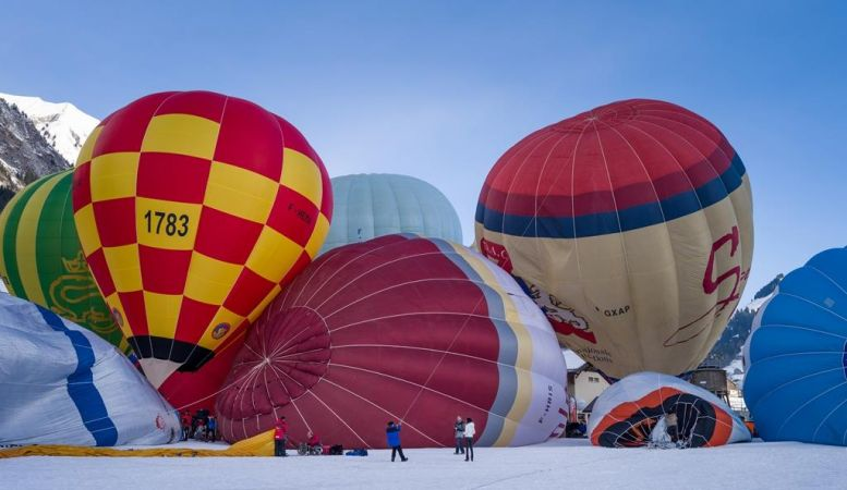 A photo of a number of colourful hot air balloons deflating on snow before a blue sky