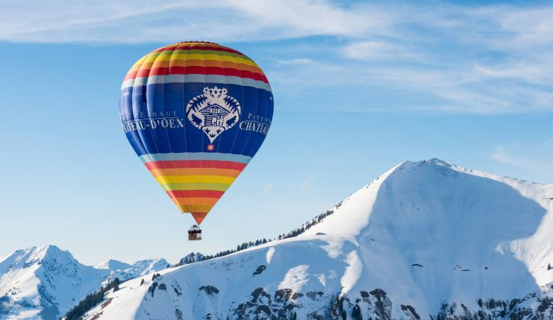 A colourful photo of Switzerland's famous hot air balloon festival, with blue sky, snow-capped mountains and a solitary balloon