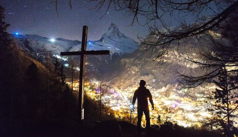 A beautiful image by Joshua Earle of the alpine village of Zermatt, lights on in the houses and the Matterhorn and mountain range behind it