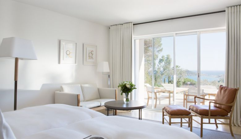 Luxury double bedroom in the Villas, decorated in white cooling tones overlooking the gardens
