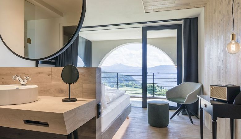Gloriette Boutique Hotel Soprabolzano - Design Bedroom with arched windows designed by noa architects, overlooking the Dolomites in South Tyrol, Italy