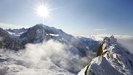A photo of the sun rising of snowy mountain peaks in the Alps