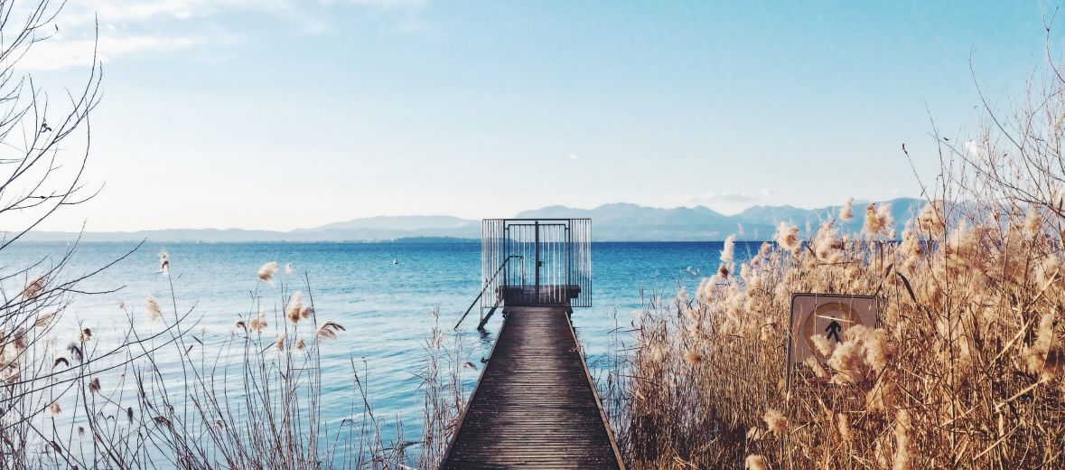 Lake Garda Italy  - blue lake with wooden jetty - close to the Vivere Suites Hotel