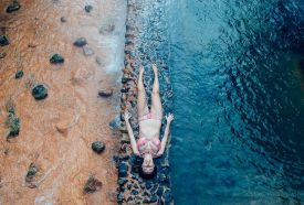 Photograph of a woman enjoying the architectural masterpiece that is São Miguel's Poça da Dona Beija thermal spring in the Azores