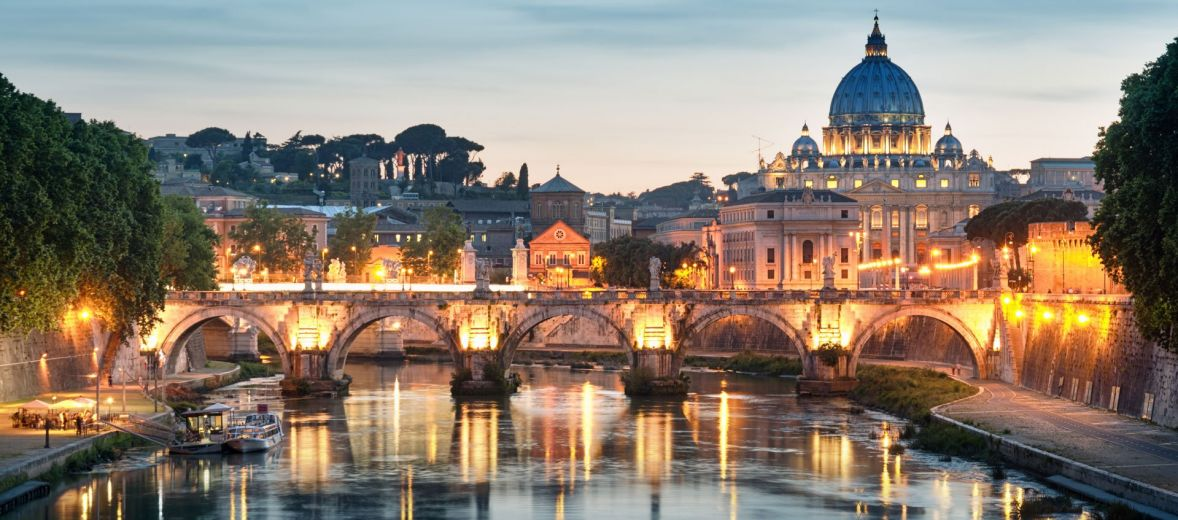 A sunset panorama of Rome on the river, lights sparkling
