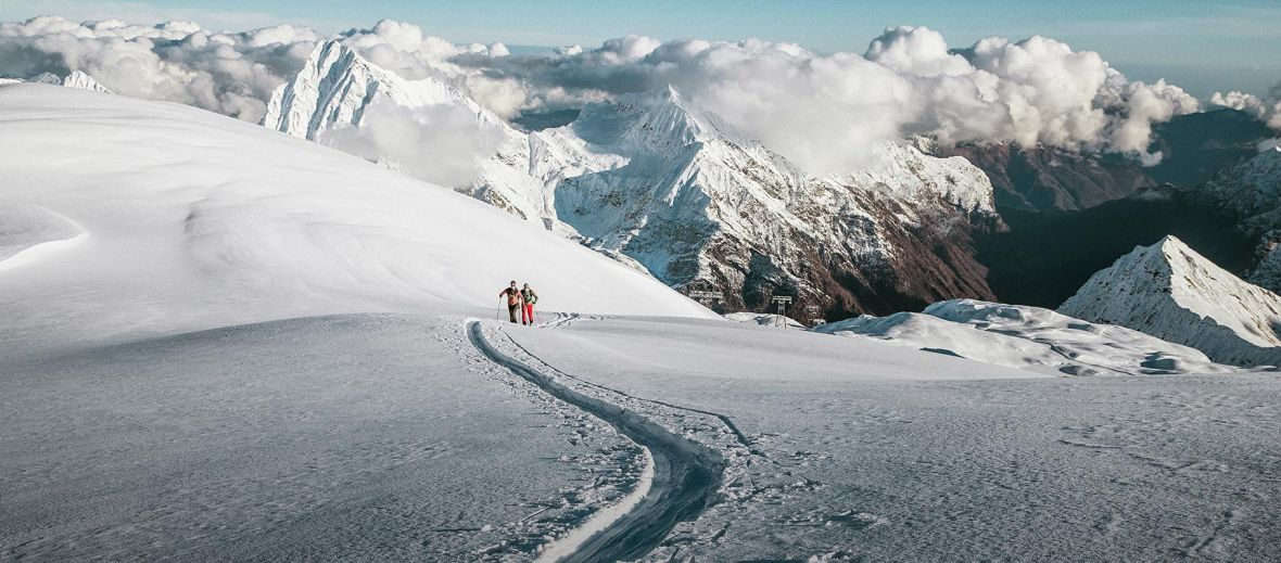 A ski trail leading through snow in the Alps