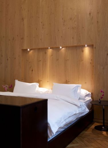 A luxe hotel bed with down lighting by Adolf Krischanitz for Hotel Altstadt's interior design of room 64