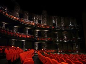 Inside Copenhagen's Royal Danish Theatre, Denmark, rows of red seats and columns mark grandeur of the stage