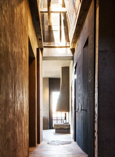 A photo of the interior of The Greenwich Hotel penthouse, by iconic interior designer Axel Vervoordt who works with wabi-sabi, the corridor and upper wall areas are putty coloured, japanese-style and stylish
