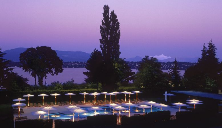 Sun set view of Lake Geneva from the pool and gardens of La Reserve Hotel & Spa Geneva, Switzerland. Purple sunsets,
