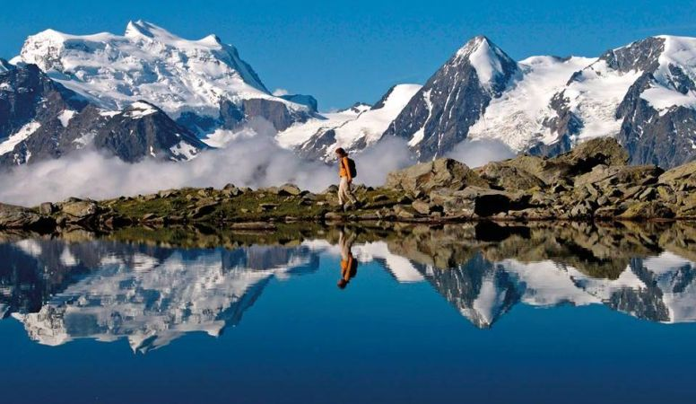 Verbier, a man traverses a stone bridge crossing with snowy mountains in the background reflected perfectly in the water of the lake that he is crossing, France